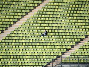 Ensam supporter sitter på en läktarsektion.