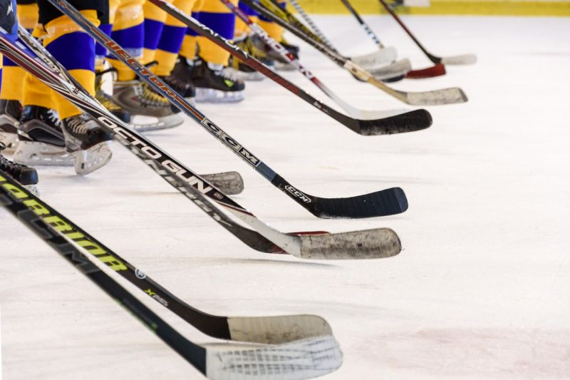 Närbild på flera hockeyklubbor i rad.