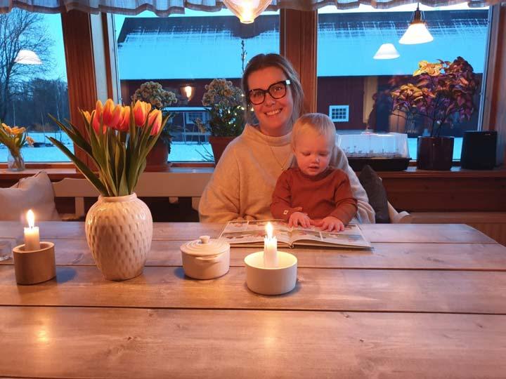 Erika och dottern Vera sitter vid ett köksbord och läser.