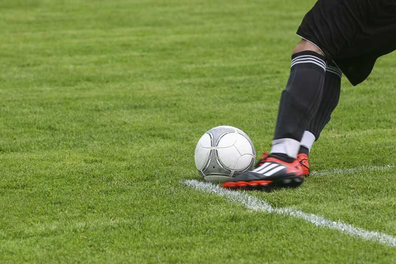 Bild på fot som sparkar på fotboll.