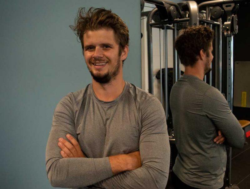 Jonathan Lindgren ler och står med händerna i kors framför en spegel. Han säger att han vill att en hälsosam livsstil och träning ska vara lika självklart som att borsta tänderna.