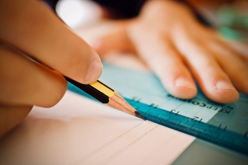 Närbild på hand som drar ett streck med blyerts efter linjal