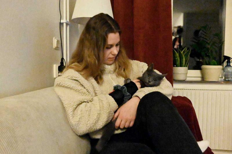 Paula sitter i en soffa med katten Essa i famnen.