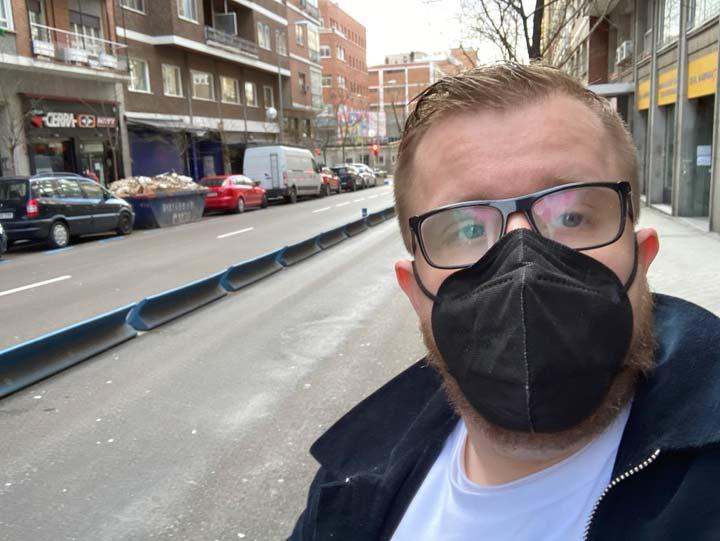 Närbild på man med munskydd, och en tom gata snett bakom.