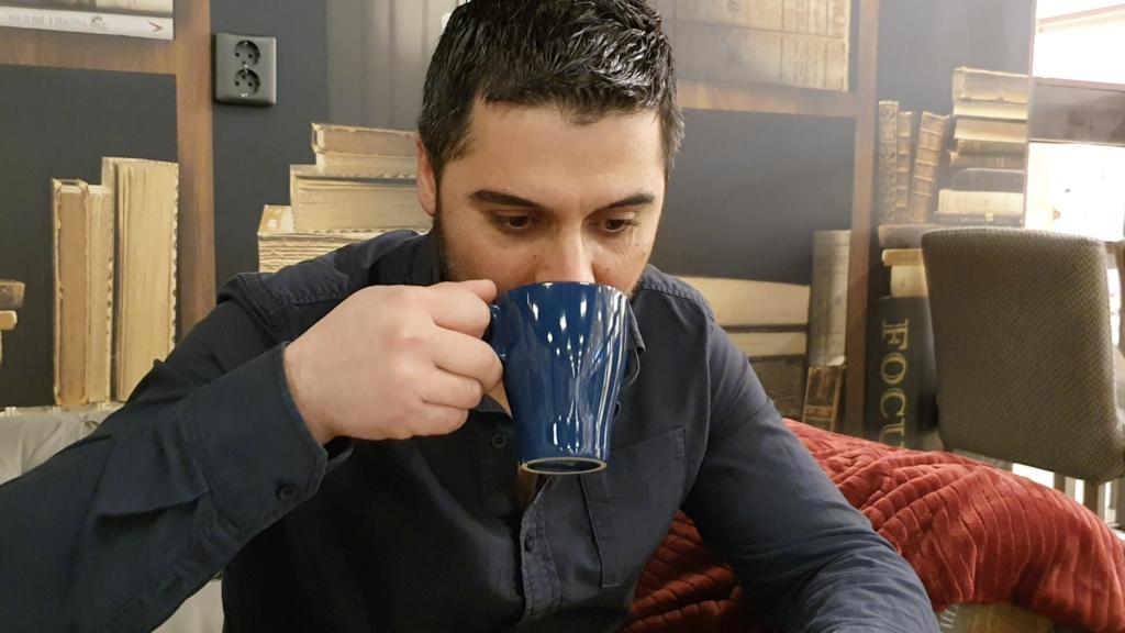 Man sitter och dricker kaffe ur en blå kopp